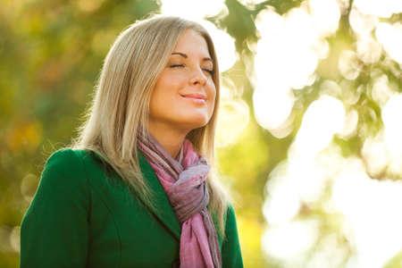 Young woman is enjoying fresh air in autumn. Фото со стока