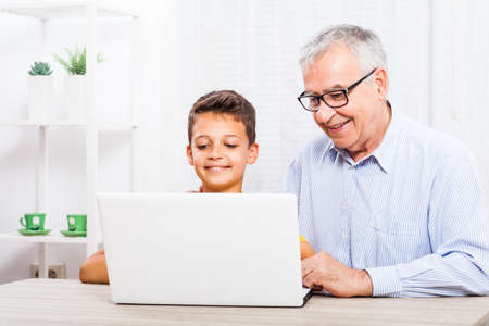 grand child: Grandfather and grandson are using laptop at home.