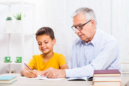 grandson: Grandfather is teaching his grandson at home.