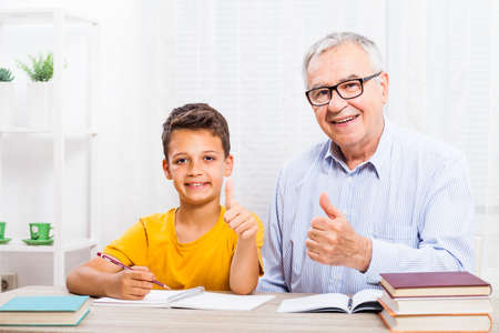 Grandfather is teaching his grandson at home.