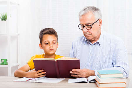 grand child: Grandfather and grandson are reading book at home. Stock Photo
