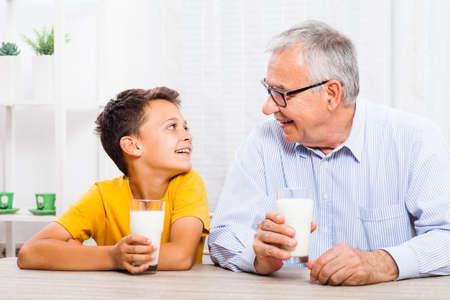 Grandfather and grandson are drinking milk at home. Healthy lifestyle.