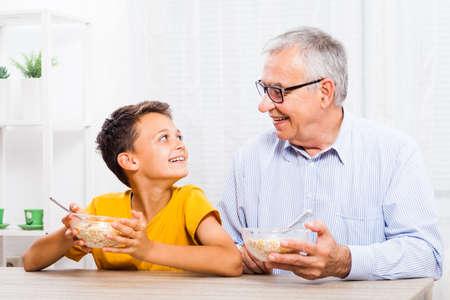 Grootvader en kleinzoon eten thuis havermout. Gezonde levensstijl.