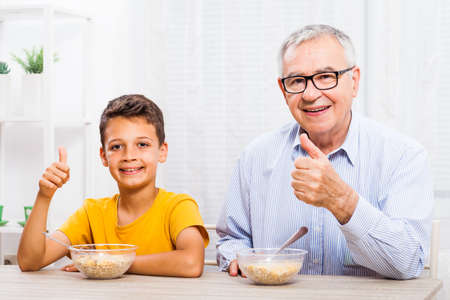grandkid: Grandfather and grandson are eating oatmeal at home. Healthy lifestyle. Stock Photo