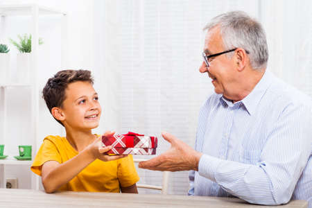 grandkid: Grandson is giving present to his grandfather.