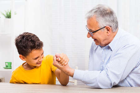 grand child: Grandfather and grandson arm wrestle at home.