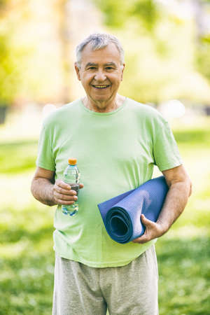 Senior man is ready for exercise in park. Active retirement. Image is intentionally toned. Stock Photo