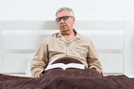 Senior man is lying in bed and he fell asleep while reading a book.