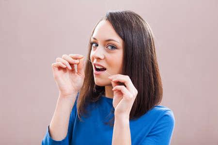 dental floss: Young woman is using dental floss. Dental hygiene concept.