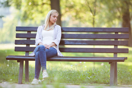 絶望の公園で座っている孤独な女性。