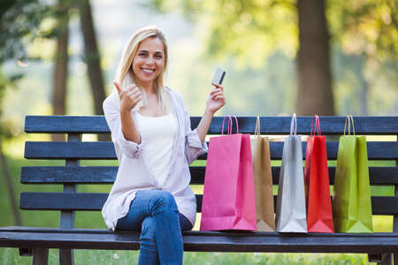 Young happy woman sitting in park after shopping and holding credit card. Stock Photo