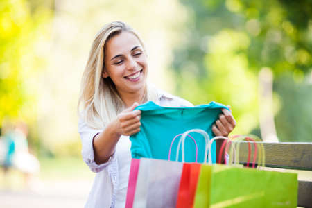 Young happy woman sitting in park after shopping and looking at clothes.