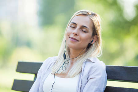 drinks after work: Young happy woman is sitting in park and listening to music.