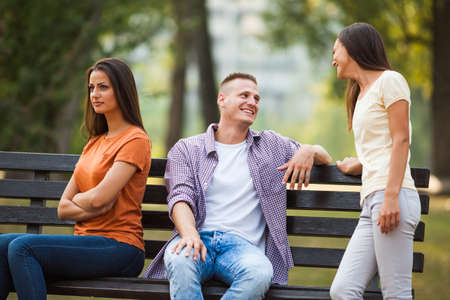 offended: Man is talking to other woman and his girlfriend is offended.