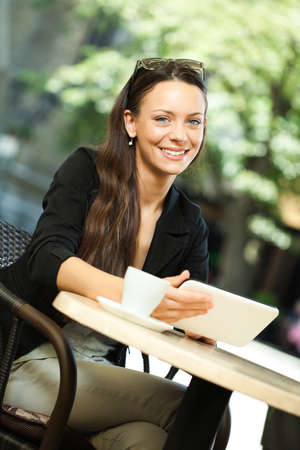 drinks after work: Young woman is using digital tablet in a cafe.
