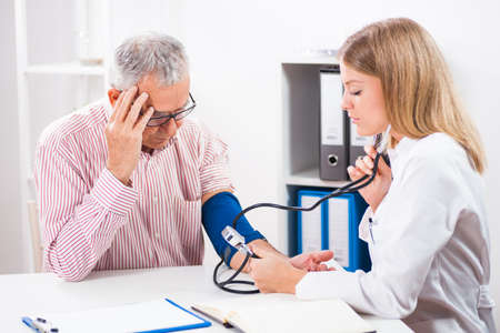 hypotension: Doctor is measuring blood pressure to her patient.