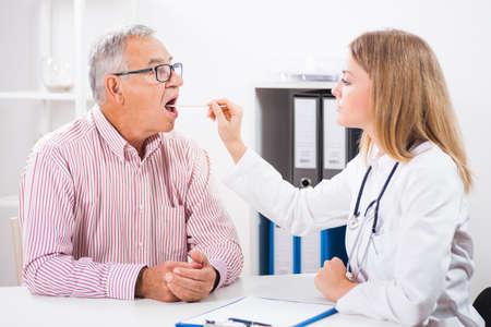 Doctor examines throat of her patient. Stock Photo