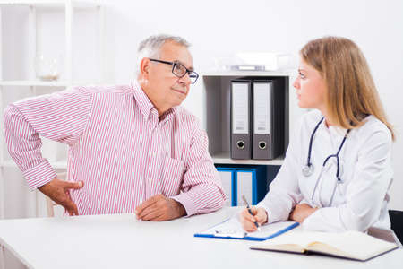 Patient is telling doctor about his health problems. He is having pain in his back.