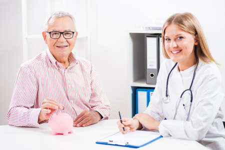 doctor money: Happy patient is saving money for his medical treatment. Stock Photo