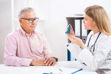 Doctor is telling to her patient how to use inhaler. Standard-Bild