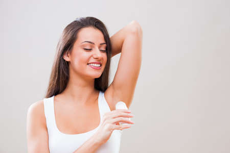 Portrait of young woman who is applying roller deodorant in her armpit. Foto de archivo