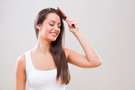 Portrait of young happy woman who is brushing her hair.