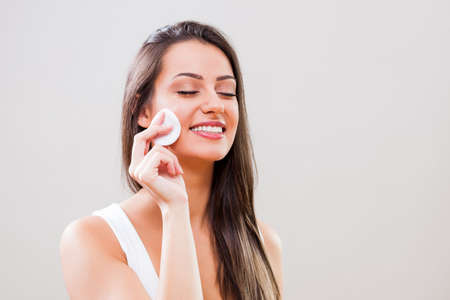 Portrait of young woman who is cleaning skin on her face. Stock Photo