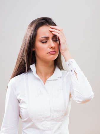 Portrait of young businesswoman who is having headache. Stock Photo
