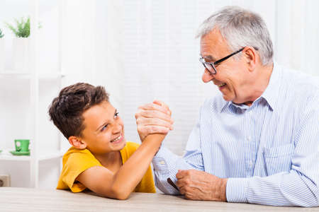 wrestle: Grandfather and grandson arm wrestle at home.