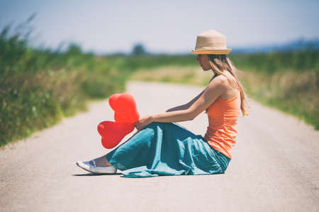 Lonely broken hearted woman is sitting on country road, intentionally toned.