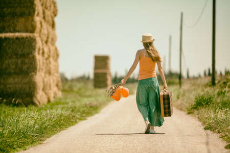 Young woman is walking on road with old suitcase, intentionally toned. Imagens
