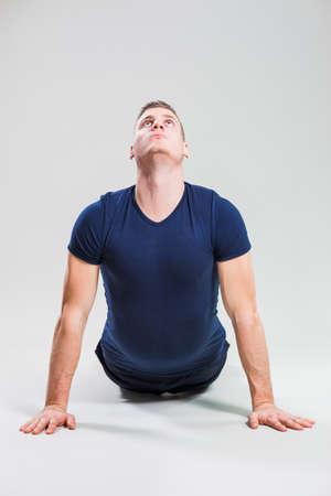bhujangasana: Studio shot image of young man who is stretching his body. Bhujangasana  Cobra Pose.