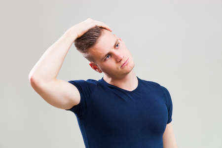 Studio shot image of young man who is stretching his body.