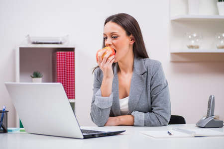 healthy snack: Young businesswoman is eating apple in her office. Stock Photo