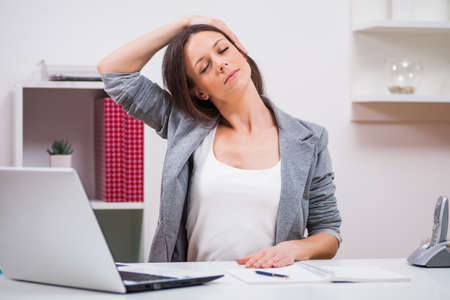 Young businesswoman is relaxing in her office. She is stretching her body. Imagens