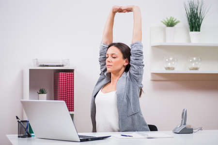 Young businesswoman is relaxing in her office. She is stretching her body. Foto de archivo