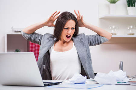 Young businesswoman is angry because she is tired of work.
