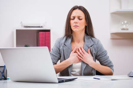 Young businesswoman is having pain in her chest at work. Stock Photo