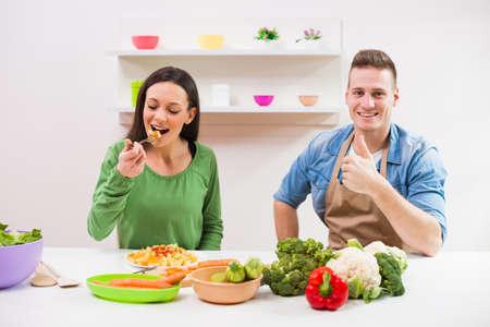 coliflor: Joven pareja de comida para cocinar en su cocina.