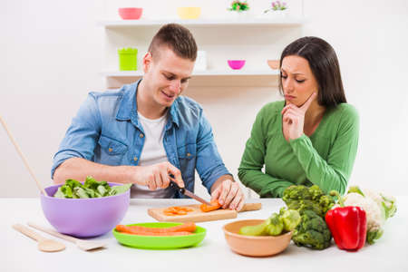 distrustful: Young couple cooking meal in their kitchen.
