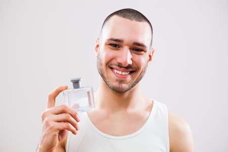 Young man is applying aftershave to his face. Stock Photo