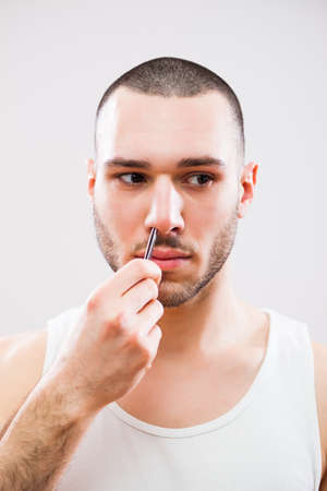 plucking: Young man is plucking nose hair with tweezers.
