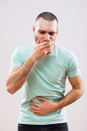 Young man is having pain in his stomach. Stock Photo