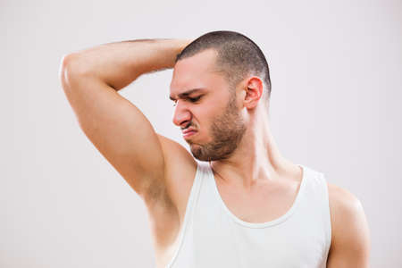 underarm: Young man is smelling his armpit before shower. Stock Photo