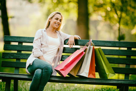 Young happy woman sitting in park after shopping. Intentionally toned. Stock Photo