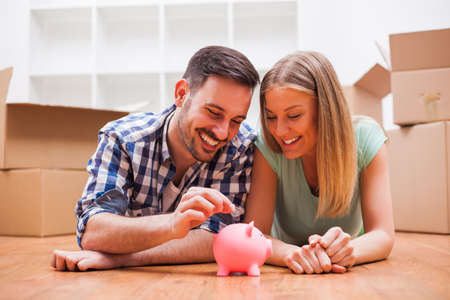 Young couple is saving money for their new home. Imagens