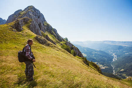 Hiker standing at viewpoint in mountain and looking at valley. Stock Photo