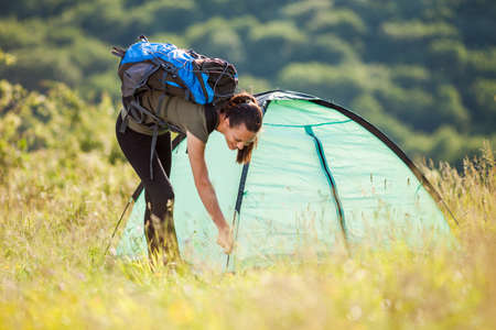 Young woman is setting up her tent in nature.