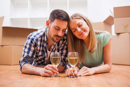 Young couple is moving in their new home. Its time for unpacking. Stock Photo
