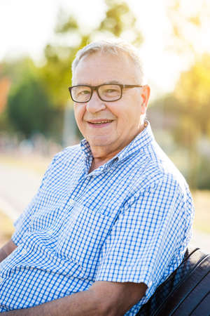 Outdoor portrait of happy senior man who is looking at camera and smiling. Imagens